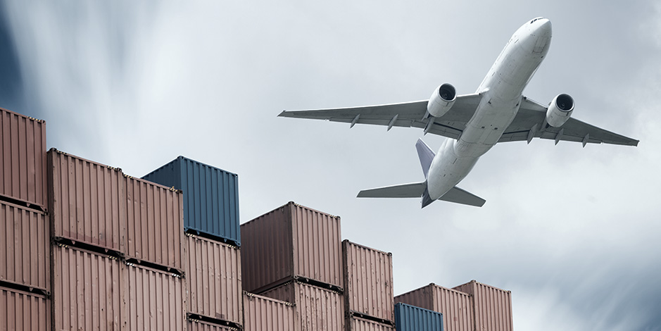 Airplane_flying_over_containers